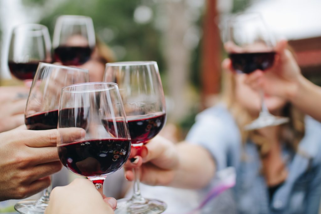 Close up image of redwine in glasses with peoples hands holding them